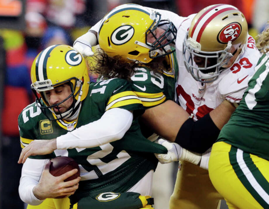 San Francisco 49ers outside linebacker Aldon Smith, right, grabs Green Bay Packers quarterback Aaron Rodgers (12) as Smith fights against the Packers offensive tackle David Bakhtiari (69) during the first half of an NFL wild-card playoff football game, Sunday, Jan. 5, 2014, in Green Bay, Wis. (AP Photo/Mike Roemer) / FR155603 AP