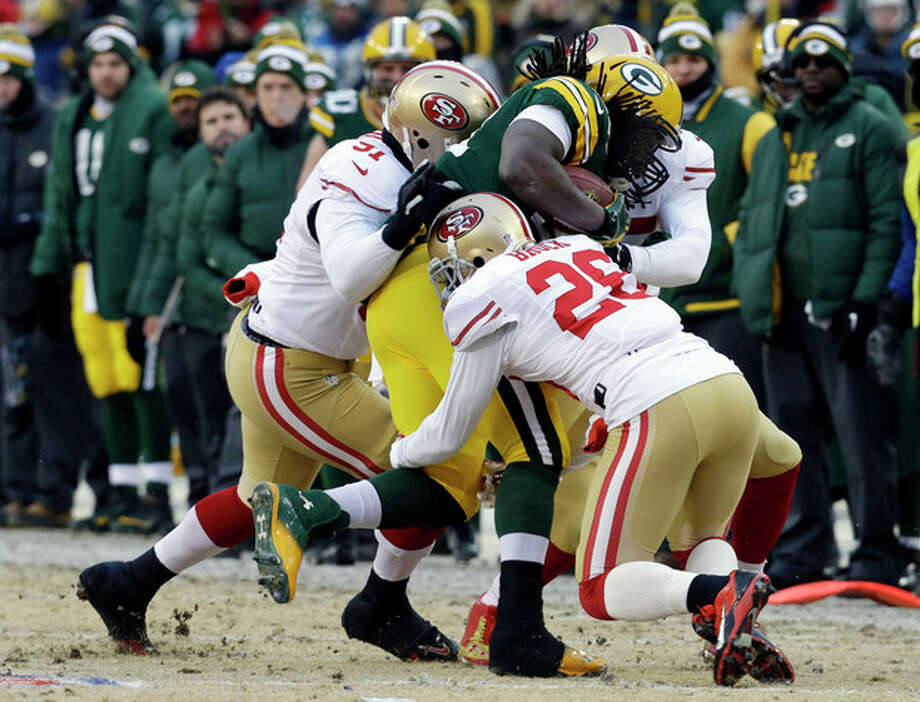 Green Bay Packers running back Eddie Lacy (27) gets tackled by San Francisco 49ers defensive end Ray McDonald (91) and cornerback Tramaine Brock (26) during the first half of an NFL wild-card playoff football game, Sunday, Jan. 5, 2014, in Green Bay, Wis. (AP Photo/Mike Roemer) / FR155603 AP