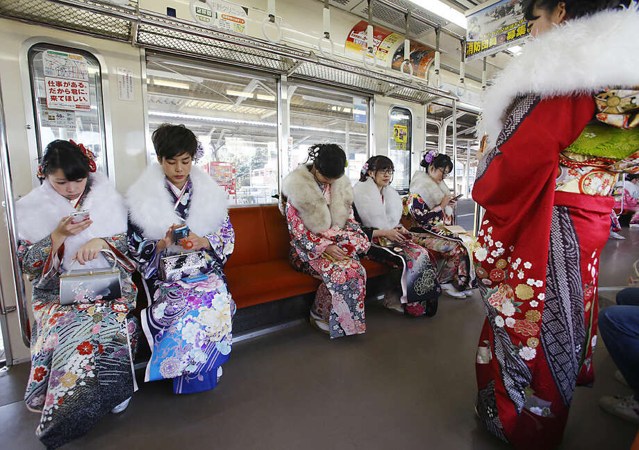 Dressed in Japanese kimonos, a group of Japanese youths who will turn 20 this year, the traditional age of adulthood in Japan, sit in a train after a Coming of Age ceremony at Toshimaen amusement park on the national holiday in Tokyo, Monday, Jan. 11, 2016. (AP Photo/Shizuo Kambayashi)