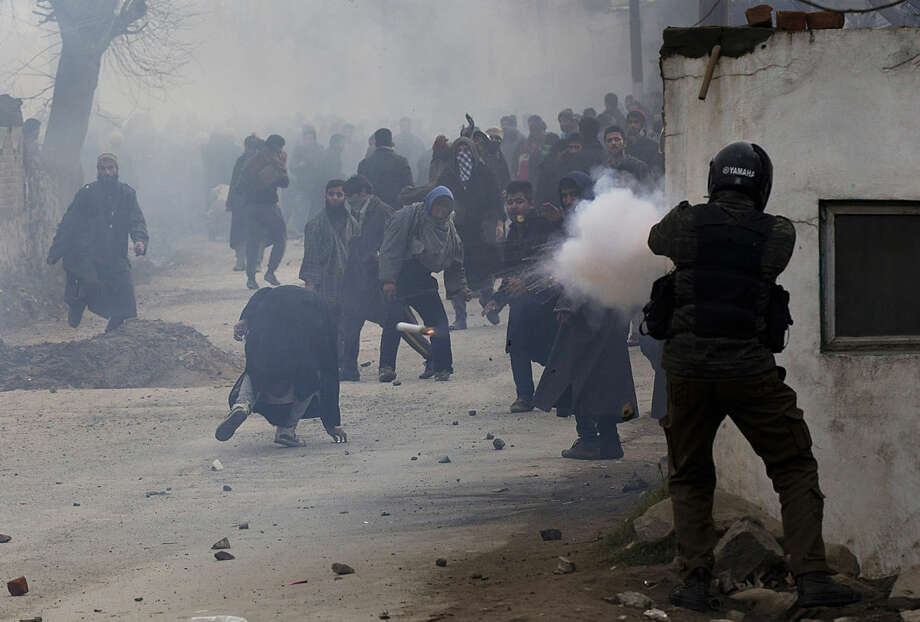 An Indian policeman fires a teargas shell as a Kashmiri Muslim, center, ducks to avoid it during the funeral procession of Sajad Ahmed Bhat, a top rebel commander on the outskirts of Srinagar, Indian controlled Kashmir, Tuesday, Jan. 12, 2016. Clashes erupted in Indian-controlled Kashmir Tuesday as police fired tear gas to stop a march by thousands of people participating in a funeral procession of a local militant killed in a gunfight with government forces. (AP Photo/Dar Yasin)