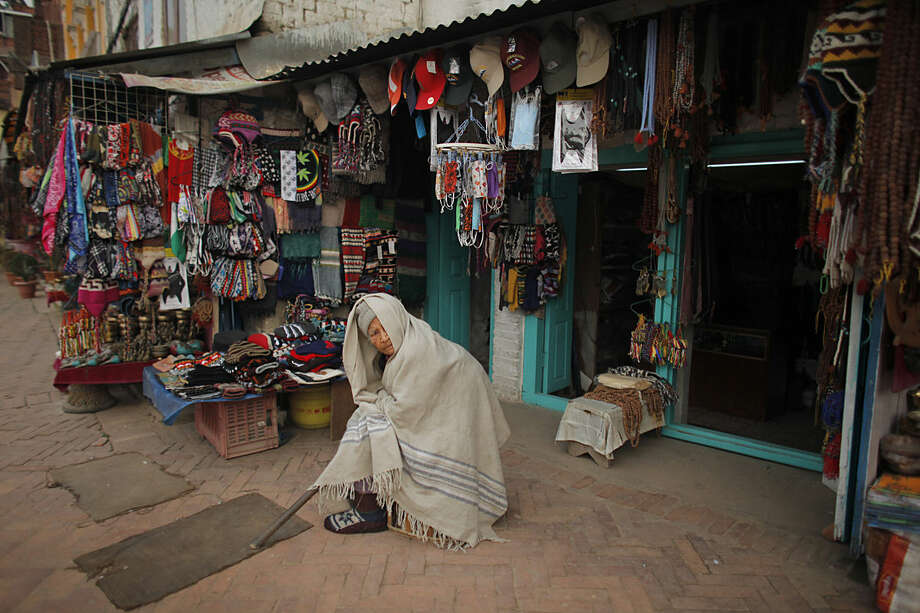 An elderly Nepalese Buddhist woman sits awaiting customers outside her shop near the world heritage site Boudhanath Stupa in Kathmandu, Nepal, Tuesday, Jan. 12, 2016. The Boudhanath Stupa was among the heritage structures that was damaged in the April 2015 earthquake.(AP Photo/Niranjan Shrestha)