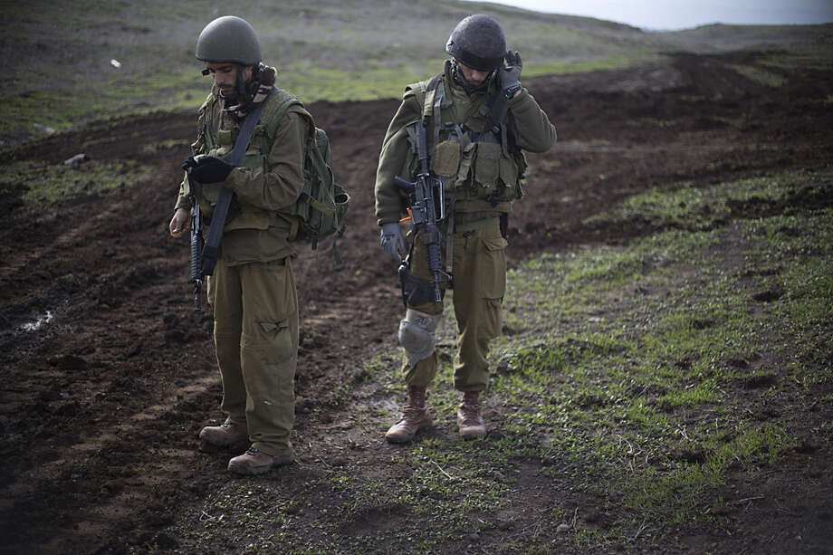 Israeli reserve soldiers from the 77 battalion of the 7th brigade from the armored corps check their gear during an exercise in the Israeli controlled Golan Heights, near the border with Syria, Monday, Jan. 11, 2016. (AP Photo/Ariel Schalit)