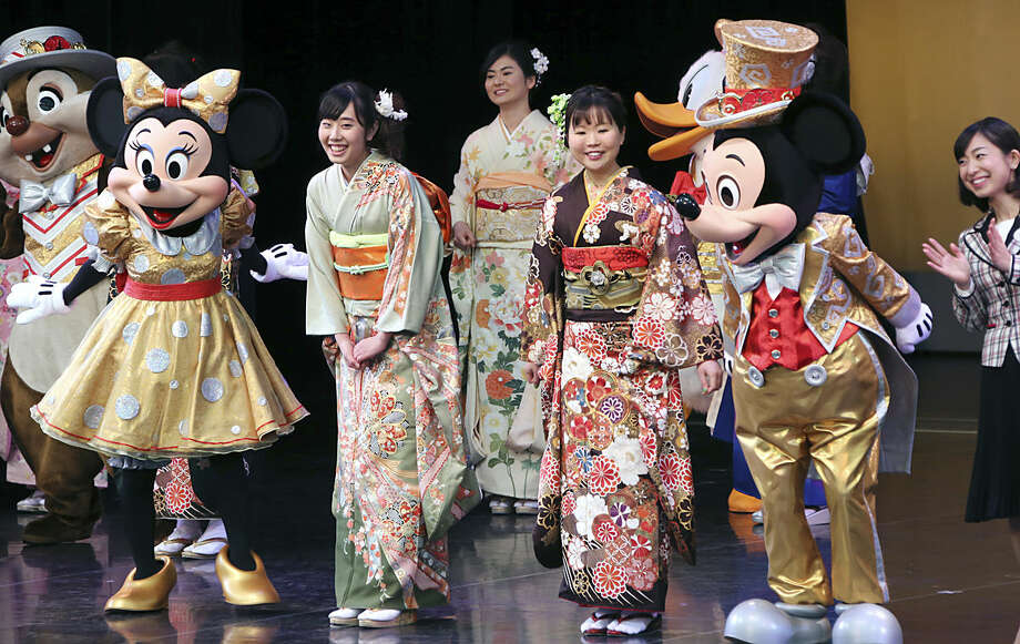 Participants, who attain the age of 20 years this year, cald in Japanese kimono pose with Mickey and Minnie Mouse on stage during a Coming of Age ceremony at Tokyo Disneyland in Urayasu, near Tokyo, Monday, Jan. 11, 2016. (AP Photo/Koji Sasahara)