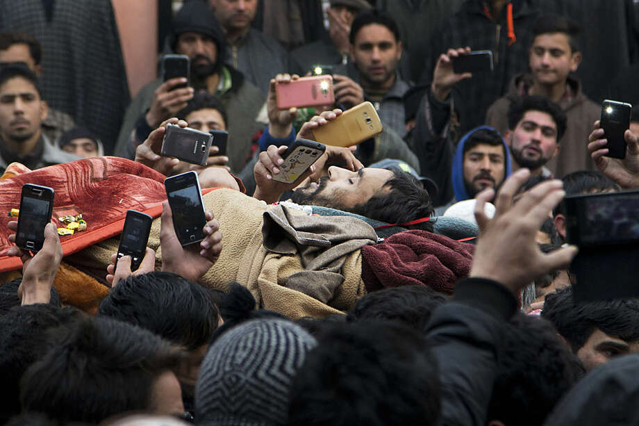 Kashmiri Muslims takes pictures with their mobile phones as they carry the body of Sajad Ahmed Bhat, a top rebel commander, during his funeral procession on the outskirts of Srinagar, Indian controlled Kashmir, Tuesday, Jan. 12, 2016. Clashes erupted in Indian-controlled Kashmir Tuesday as police fired tear gas to stop a march by thousands of people participating in a funeral procession of a local militant killed in a gunfight with government forces. (AP Photo/Dar Yasin)