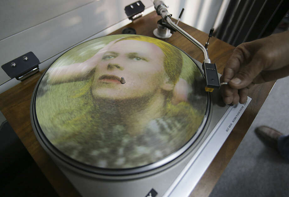 Rene Rivo, a Filipino David Bowie fan, plays a picture disc of Bowie's Hunky Dory on a turntable at his shop in suburban Paranaque, south of Manila, Philippines Tuesday, Jan. 12, 2016. Bowie, the chameleon-like star who transformed the sound - and the look - of rock with his audacious creativity and his sexually ambiguous makeup and costumes, died of cancer Sunday, Jan. 10. (AP Photo/Aaron Favila)
