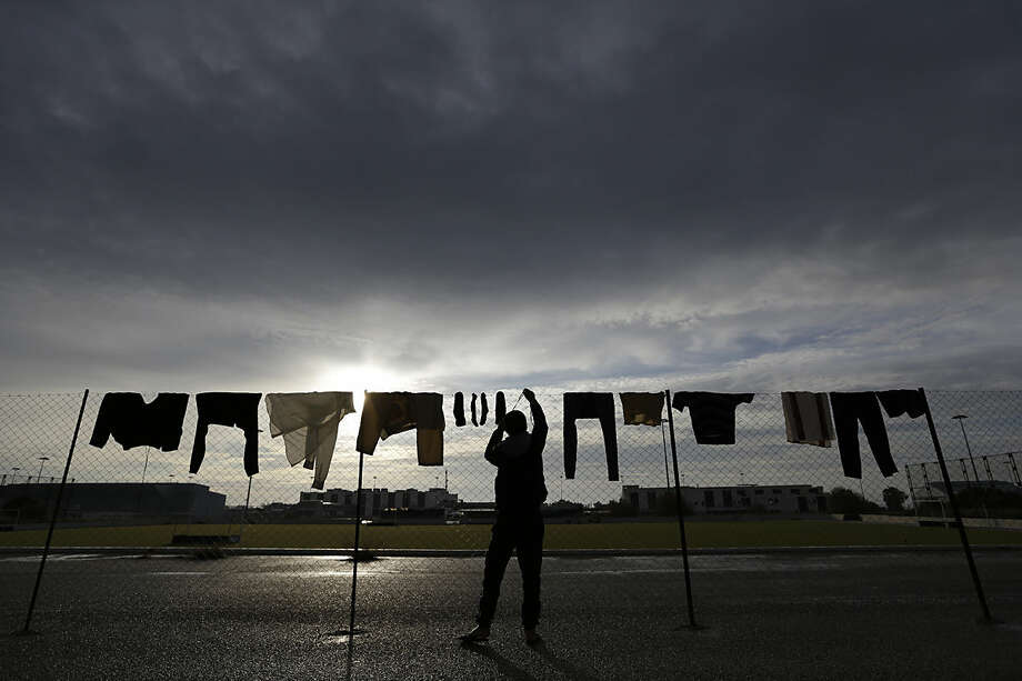 In this photo taken on Sunday, Jan. 10, 2016 a man from Libya hangs his wet shoe laces on a fence at the Hellenikon shelter, a former Olympic field hockey venue, in southern Athens. A tightening of border controls closer to the promised lands of Germany and Sweden has left thousands trapped and destitute in the last place most want to be _ financially-wrecked Greece, which is Europe's main immigration gateway. (AP Photo/Thanassis Stavrakis)