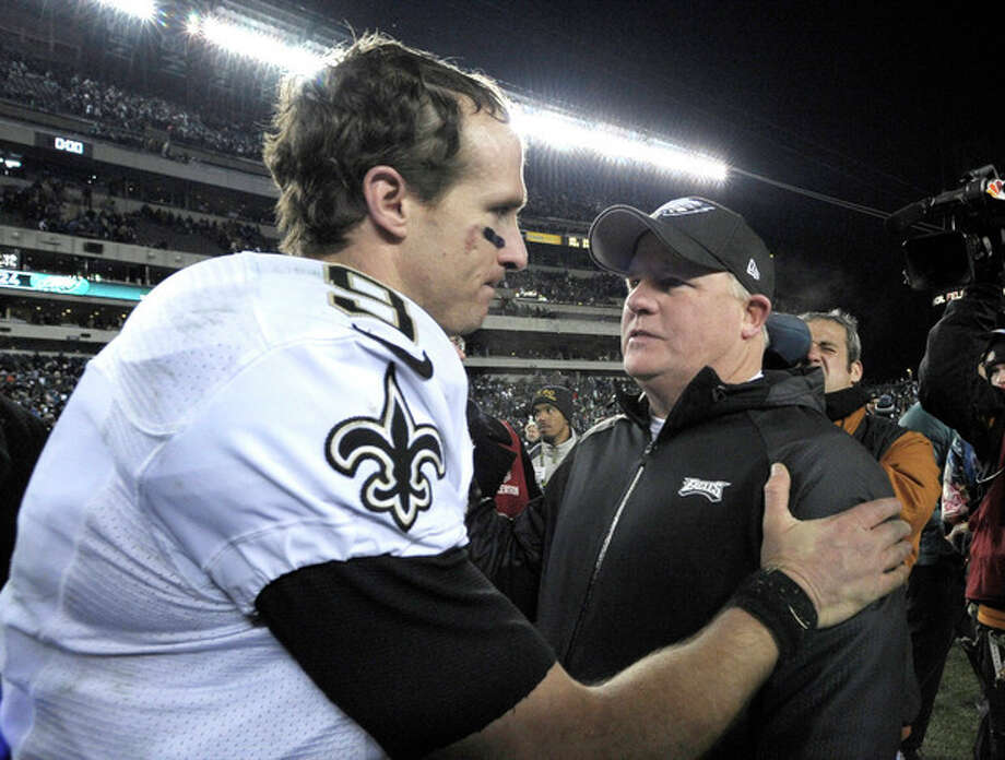 Philadelphia Eagles head coach Chip Kelly, right, meets with New Orleans Saints' Drew Brees after an NFL wild-card playoff football game, Saturday, Jan. 4, 2014, in Philadelphia. New Orleans won 26-24. (AP Photo/Michael Perez) / FR168006 AP