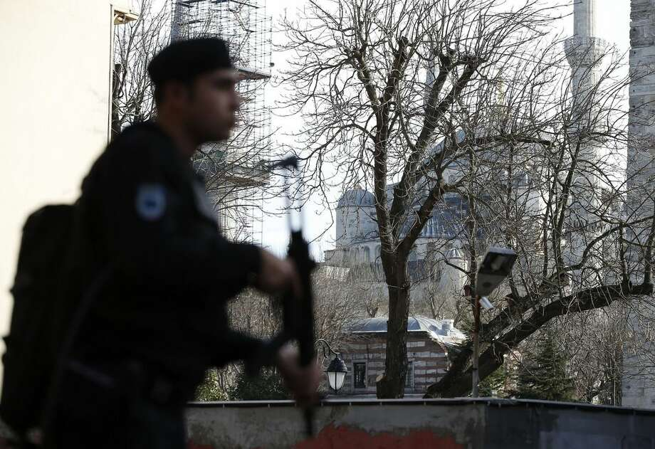 A policemen patrols at the Sultanahmet district after an explosion as the Blue Mosque is seen in the background in Istanbul, Tuesday, Jan. 12, 2016. The explosion in a historic district of Istanbul popular with tourists killed 10 people and injured 15 others Tuesday morning, the Istanbul governor's office said. (AP Photo/Emrah Gurel)
