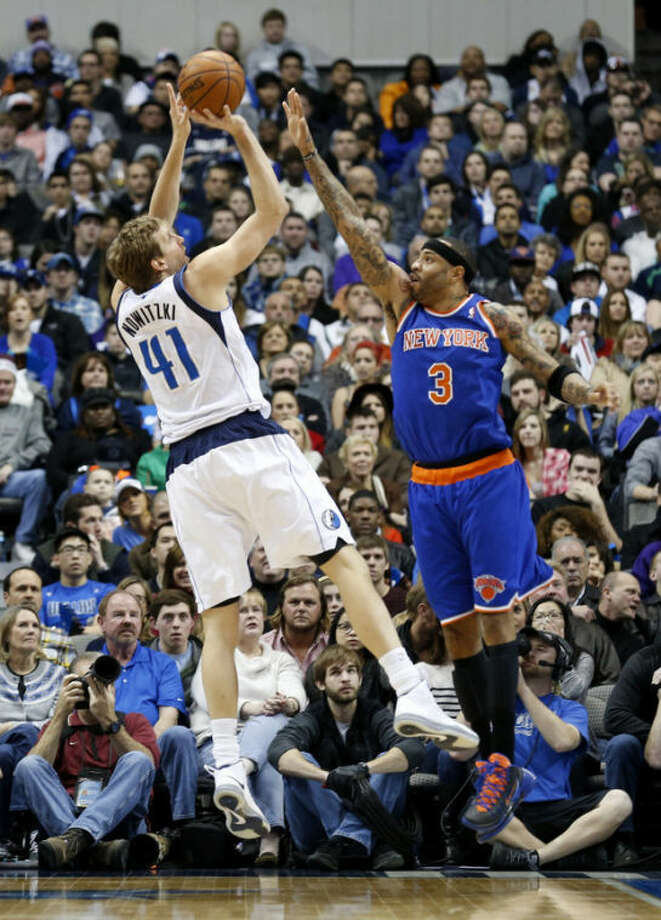 Dallas Mavericks forward Dirk Nowitzki (41), of Germany, takes a shot over New York Knicks forward Kenyon Martin (3) during the first half of an NBA basketball game, Sunday, Jan. 5, 2014, in Dallas. (AP Photo/Sharon Ellman)