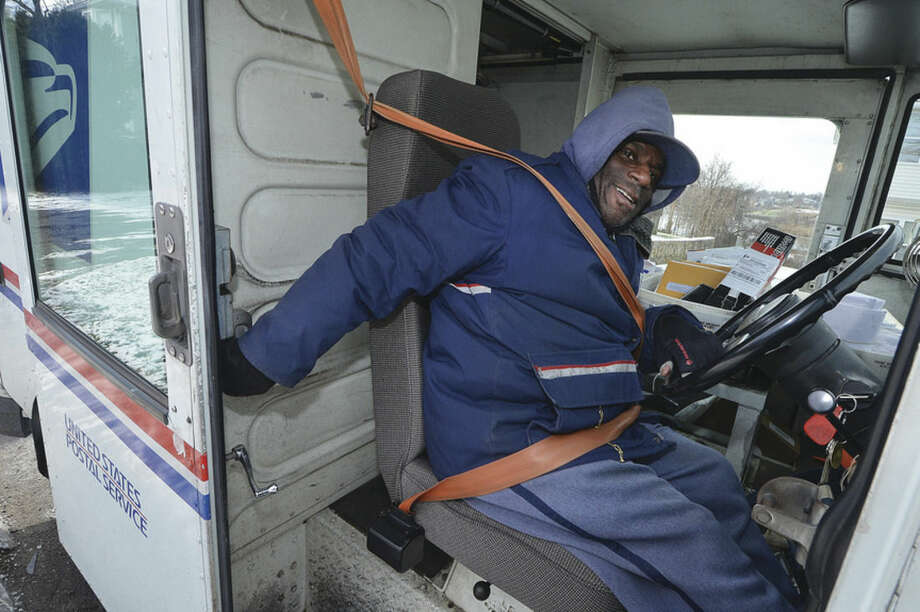 Hour photo/Alex von KleydorffLetter Carrier Eric Gray is bundled up and gets back in his vehicle as he makes his way to almost 300 stops during his route delivering the mail during freezing temperatures in Norwalk on Wednesday.