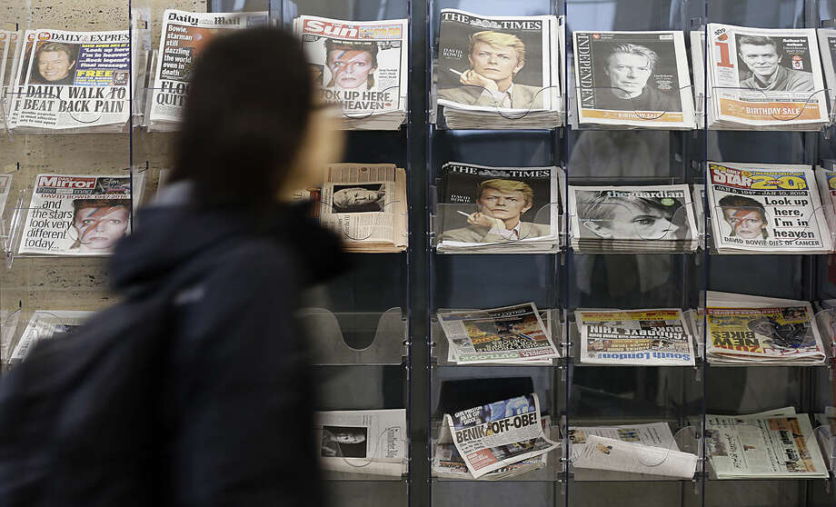 A women passes a display of newspapers that show a picture of David Bowie on the front in London, Tuesday, Jan. 12, 2016. Bowie, the other-worldly musician who broke pop and rock boundaries with his creative musicianship, nonconformity, striking visuals and a genre-spanning persona he christened Ziggy Stardust, died of cancer Sunday aged 69. (AP Photo/Frank Augstein)
