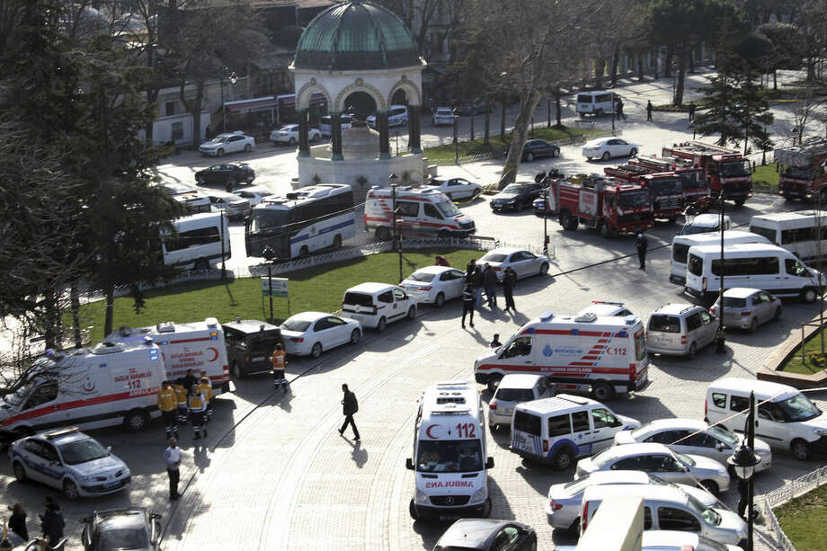 "Ambulances and firefighters stationed near the city's landmark Sultan Ahmed Mosque or Blue Mosque after an explosion at Istanbul's historic Sultanahmet district, which is popular with tourists, Tuesday, Jan. 12, 2016. The Istanbul governor's office says the explosion at the city's historic Sultanahmet district has killed least 10 people. A statement says 15 other people were injured in Tuesday's blast. The cause of the explosion is under investigation, but state-run TRT television says it was likely caused by a suicide bomber. The monument in the background is ""German Fountain."" (IHA via AP) TURKEY OUT"
