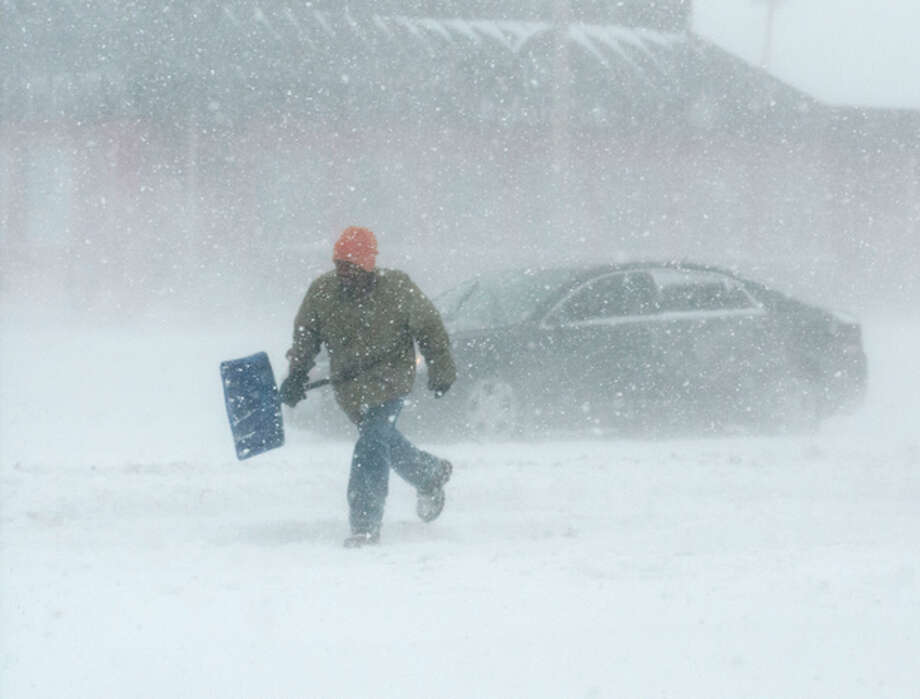A man carrying a snow shovel walks along Market Street in Champaign, Ill., on Sunday, Jan. 5, 2014. Icy, snow-covered roads and high winds made travel treacherous from the Dakotas and Michigan to Missouri as much of the nation braced for the next winter wallop: a dangerous cold that could break records. (AP Photo/The News-Gazette, Holly Hart) MANDATORY CREDIT / The News-Gazette