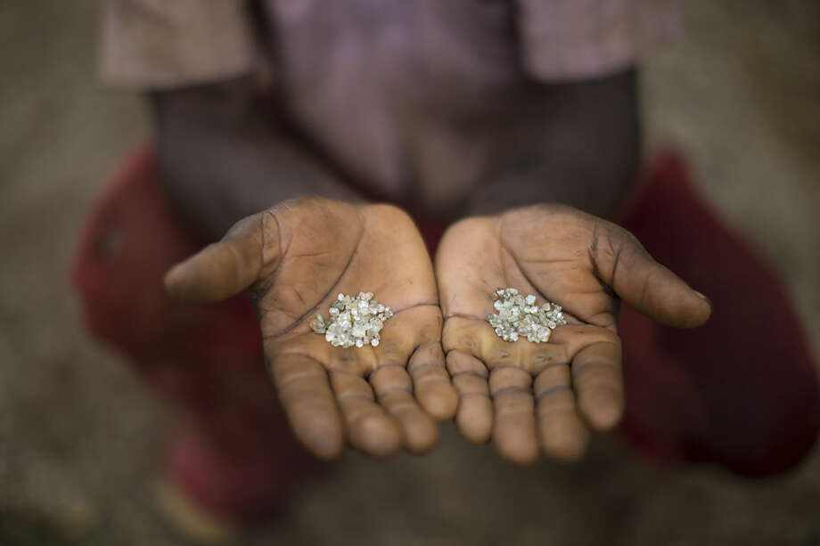 In this Nov. 19, 2015 photo, an artisanal miner shows the diamonds he and his group found in an abandoned mine in Areinha, Minas Gerais state, Brazil. The area has been explored for the precious stone since the time of slavery, and up to a couple of years ago, multinational mining companies extracted the stone without care for the land or the Jequitinhonha river that crosses the region. (AP Photo/Felipe Dana)