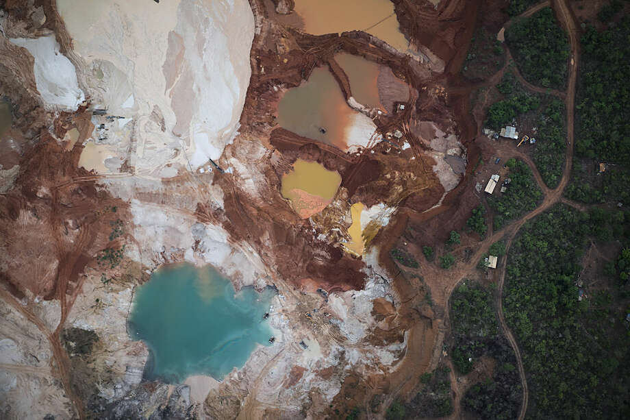 This Nov. 18, 2015 photo shows an area that was destroyed by diamond mining at an abandoned mine in Areinha, Minas Gerais state, Brazil. The devastated area known as Areinha is a no man's land where small groups of artisanal miners try their luck in the craters left behind by multinational mining companies. (AP Photo/Felipe Dana)