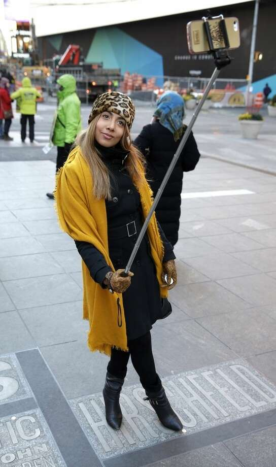 Sandy Johal uses a selfie stick to take a picture of herself in Times Square in New York, Thursday, Jan. 8, 2015. Relatively new gadgets called selfie sticks make it easy to take your own wide-angled self-portraits or group shots. Fans say the expandable rods, which allow users to hold their cellphones a few feet away, are the ultimate convenience: no more bothering passers-by to take pictures, no more fretting about strangers taking lousy shots or running off with a pricey iPhone. (AP Photo/Seth Wenig)