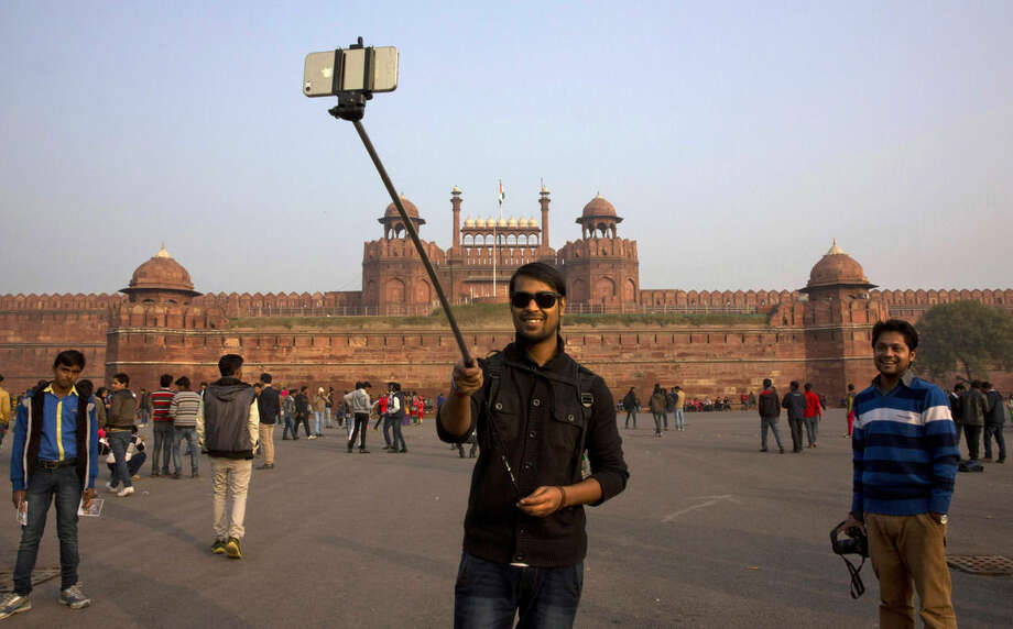 An Indian tourist uses a selfie stick to take a photograph in front of the historical Red Fort monument in New Delhi, India, Tuesday, Jan. 6, 2015. Selfie sticks have become popular among tourists because you don't have to ask strangers to take your picture, and you can capture a wide view in a selfie without showing your arm. (AP Photo /Manish Swarup)