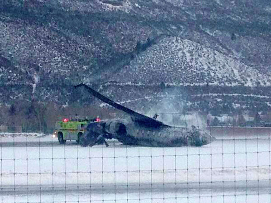 Emergency crews respond as a small plane lies on a runway at Aspen Airport in western Colorado after it crashed upon landing Sunday, Jan. 5, 2014. Emergency crews are responding to a fiery plane crash at Aspen Airport in western Colorado. (AP Photo/Corey Morris-Singer) / AP