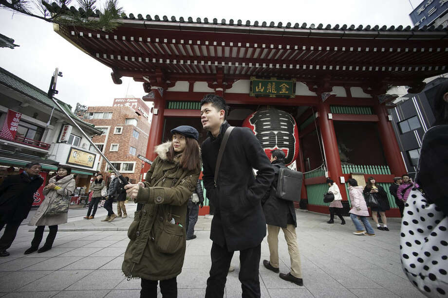 Huang Hsin, left, and Lu Yz-che, right, from Taiwan take a photo with selfie stick at the gate of Sensoji temple in Asakusa District in Tokyo Wednesday, Jan. 7, 2015. Selfie sticks have become popular among tourists because you don't have to ask strangers to take your picture, and you can capture a wide view in a selfie without showing your arm. (AP Photo/Eugene Hoshiko)