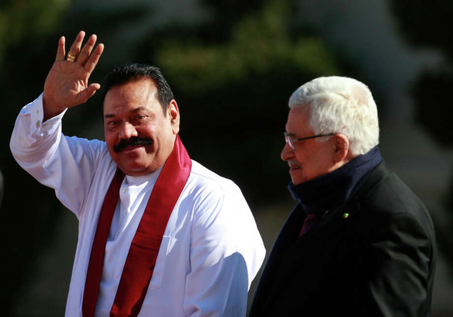 Sri Lanka's President Mahinda Rajapaksa, left, waves as he walks with Palestinian President Mahmoud Abbas during a welcoming ceremony in the West Bank city of Ramallah, Monday, Jan. 6, 2014. Rajapaksa is on a tour of the Middle East where he will meet the leaders of the Palestinian Authority and Israel. (AP Photo/Majdi Mohammed) / AP