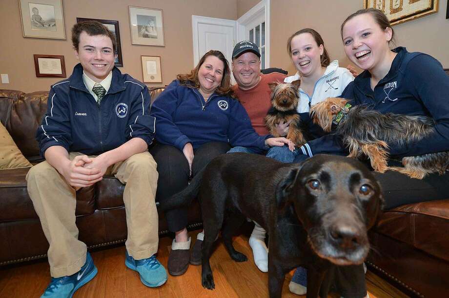 Rexy, the black Labrador, tries to get in the Craven family photo. From left to right is David, Claire, Eric and Elizabeth, with Mae, Amanda and Madeline and their two Yorkshire terriers.