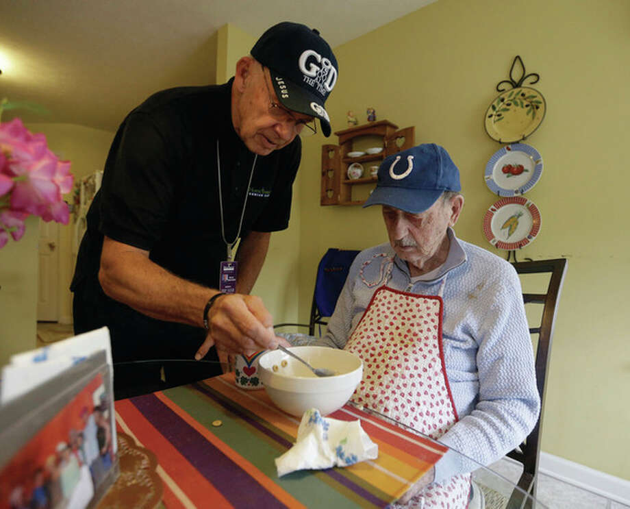 In this Nov. 21, 2103 photo, caregiver Warren Manchess, 74, left, helps Paul Gregoline, 92, with a meal, in Noblesville Ind. Burgeoning demand for senior services like home health aides is being met by a surprising segment of the workforce: Other seniors. Twenty-nine percent of so-called direct-care workers are projected to be 55 or older by 2018 and in some segments of that population older workers are the single largest age demographic. With high rates of turnover, home care agencies have shown a willingness to hire older people new to the field who have found a tough job market as they try to supplement their retirement income. (AP Photo/Darron Cummings) / AP