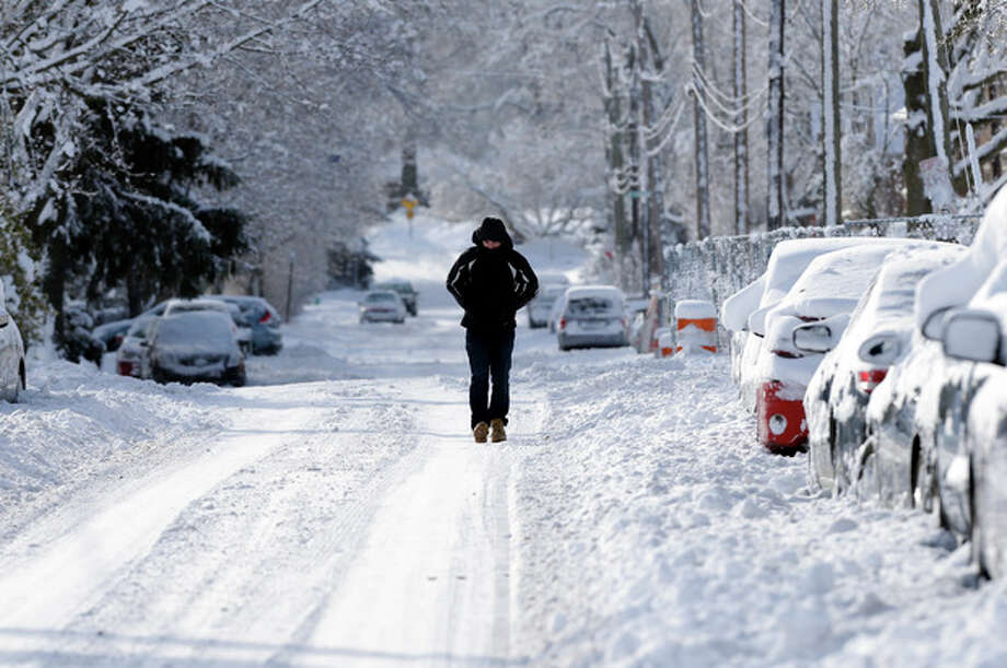 A pedestrian makes their way along a snow packed street in Indianapolis Monday, Jan. 6, 2014 as temperatures hovered around 10 below zero. More than 12 inches of snow fell on Sunday. (AP Photo/Michael Conroy) / AP