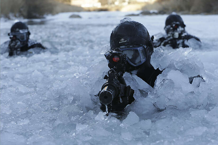South Korea's Amry Special Warfare Command (SWC) soldiers aim their machine guns in a frozen river during a winter exercise in Pyeongchang, South Korea, Thursday, Jan. 8, 2015. About 200 SWC soldiers participated in this routine two-week winter drill. (AP Photo/Ahn Young-joon)