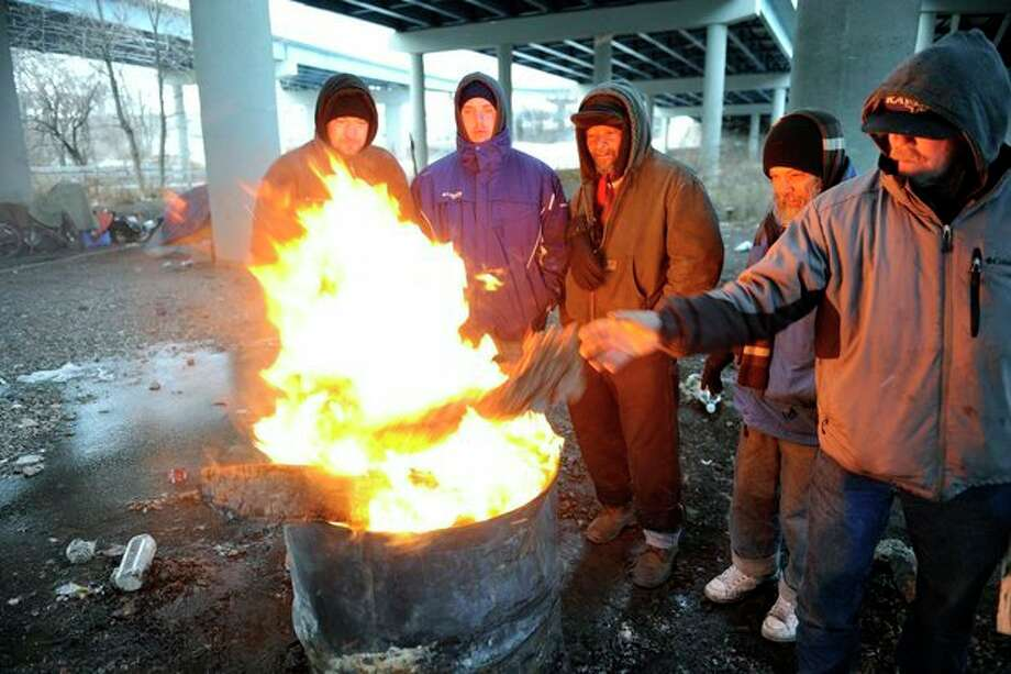 Michael Best, right, and others who identified themselves as homeless use donated wood and a fire barrel to keep warm Monday, Jan. 6, 2014, in Knoxville, Tenn. Monday's expected high temperature in Knoxville of around 24 degrees came hours before dawn, and is expected to fall into the single digits for most of East Tennessee. (AP Photo/Knoxville News Sentinel, Michael Patrick) / Knoxville News Sentinel