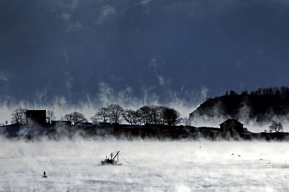 A fisherman works aboard a trawler passing House Island in Casco Bay of Portland, Maine, where the temperature at dawn was minus-9 degrees, Thursday, Jan. 8, 2014. Sea smoke is a fog formed by extremely cold air moving across warmer water. (AP Photo/Robert F. Bukaty)