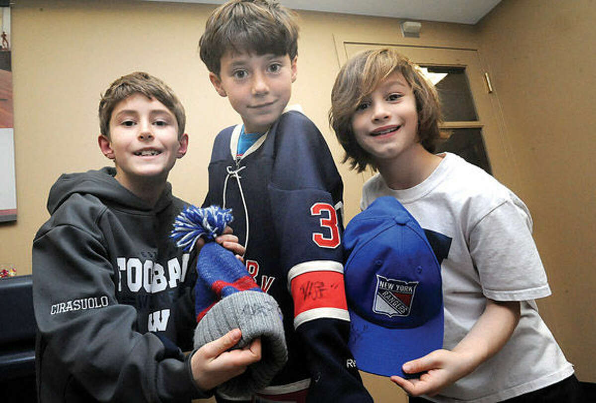 Rangers fans, Ryan Cirasuolo 10, Elliot Klein 10 and Shane Sanders 8 with signed merchandise from New York Rangers players Derek Stepan and Ryan McDonagh who were at the Westport, CT Chase Branch on Tuesday. Hour photo/Matthew Vinci
