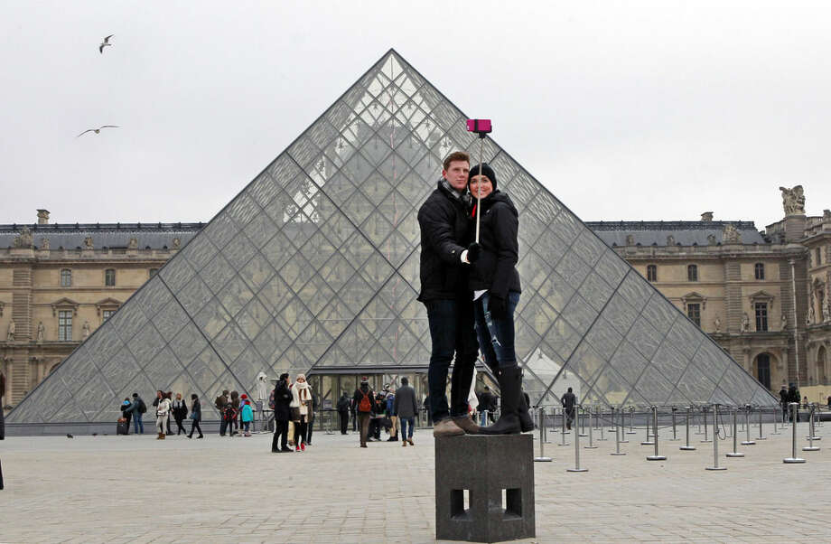 Chris Baker and Jennifer Hinson from Nashville, Tennessee, use a selfie stick in front of the Louvre Pyramide in Paris, Tuesday, Jan. 6, 2015. Selfie sticks have become enormously popular among tourists because you don't have to ask strangers to take your picture, and unlike hand-held selfies, you can capture a wider view without showing your arm. But some people find selfie sticks obnoxious, arguing that they detract from the travel experience. (AP Photo/Remy de la Mauviniere)