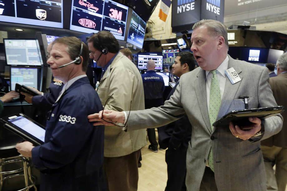 Mathias Roberts, right, reaches out to a fellow trader on the floor of the New York Stock Exchange, Tuesday, Jan. 12, 2016. U.S. stocks are opening higher, led by gains in big technology companies, which have had a rough start to the year. (AP Photo/Richard Drew)