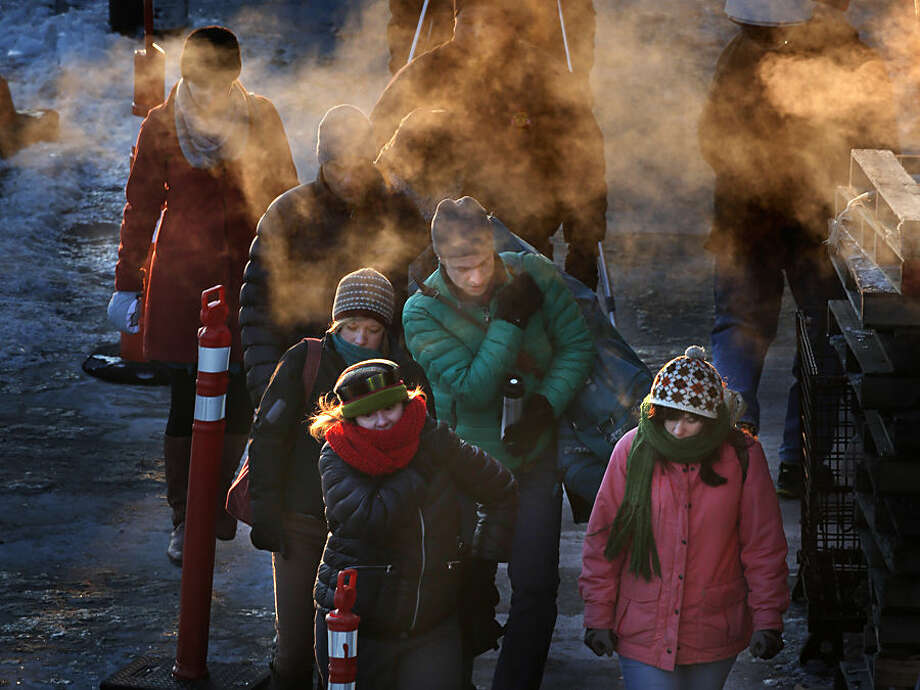 Commuters leave the Casco Bay Ferry terminal after arriving in Portland, Maine, where the temperature at dawn was minus 9 degrees F, Thursday, Jan. 8, 2015. Dangerously cold air has sent temperatures plummeting around the U.S. (AP Photo/Robert F. Bukaty)