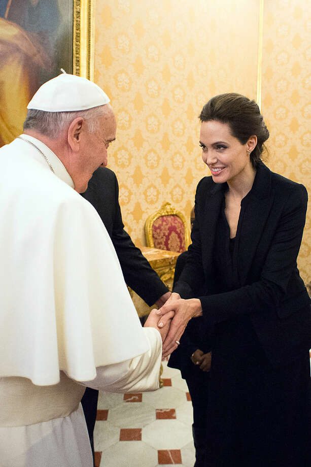 "Pope Francis greets Angelina Jolie, at the Vatican, Thursday, Jan. 8, 2015. The actress, director and U.N. special envoy met briefly with Pope Francis Thursday in the Apostolic Palace after screening her film ""Unbroken"" to some Vatican officials and ambassadors. (AP Photo/L'Osservatore Romano, Pool)"