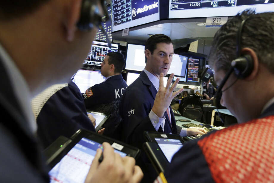 Specialist John McNierney, center, works at his post on the floor of the New York Stock Exchange, Tuesday, Jan. 12, 2016. U.S. stocks are opening higher, led by gains in big technology companies, which have had a rough start to the year. (AP Photo/Richard Drew)