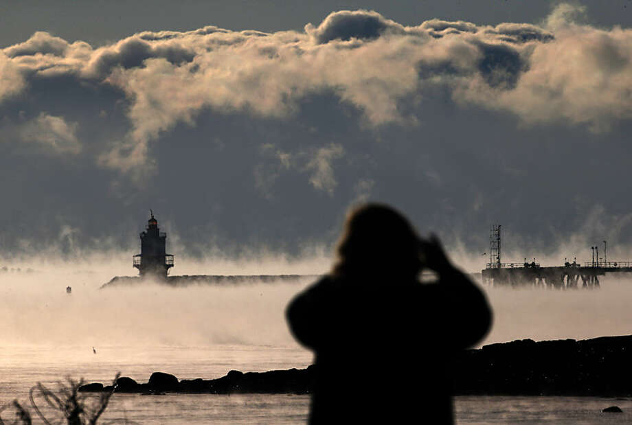 A woman photographs the sea smoke rising from the harbor in Portland, Maine, where the temperature at dawn was minus 9 degrees F, Thursday, Jan. 8, 2015. Dangerously cold air has sent temperatures plummeting around the U.S. (AP Photo/Robert F. Bukaty)