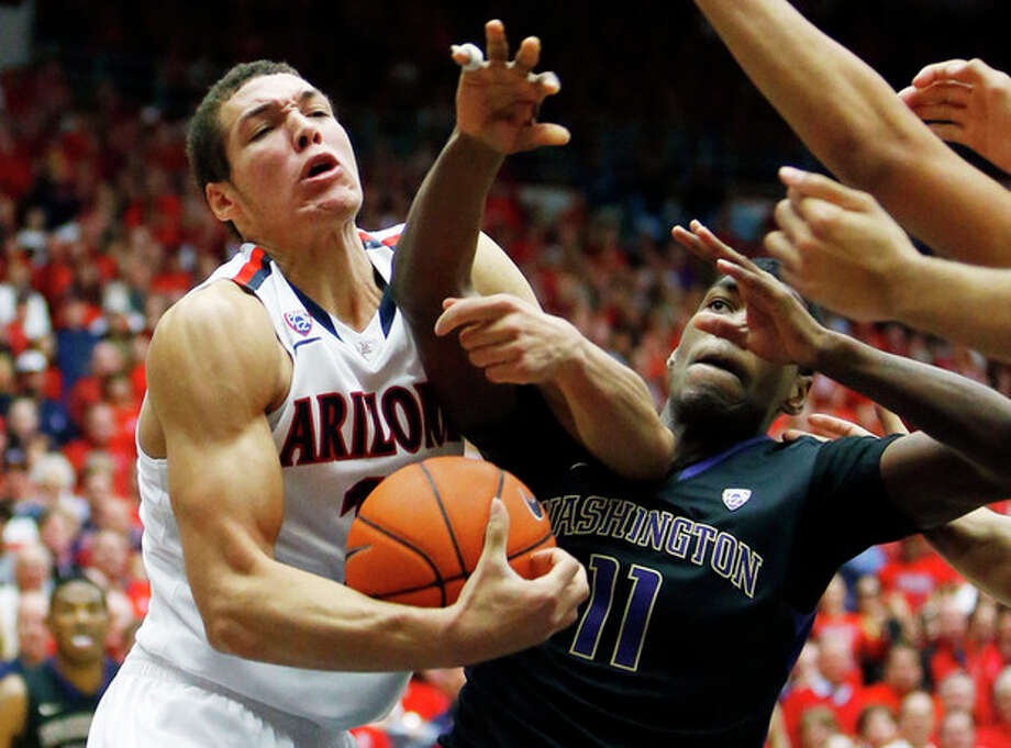 Arizona forward Aaron Gordon (11) and Washington guard Mike Anderson (11) fight for a rebound during the second half of an NCAA college basketball game Saturday, Jan. 4, 2014, in Tucson, Ariz. (AP Photo/The Arizona Republic, David Kadlubowski) MARICOPA COUNTY OUT; MAGS OUT; NO SALES / The Arizona Republic