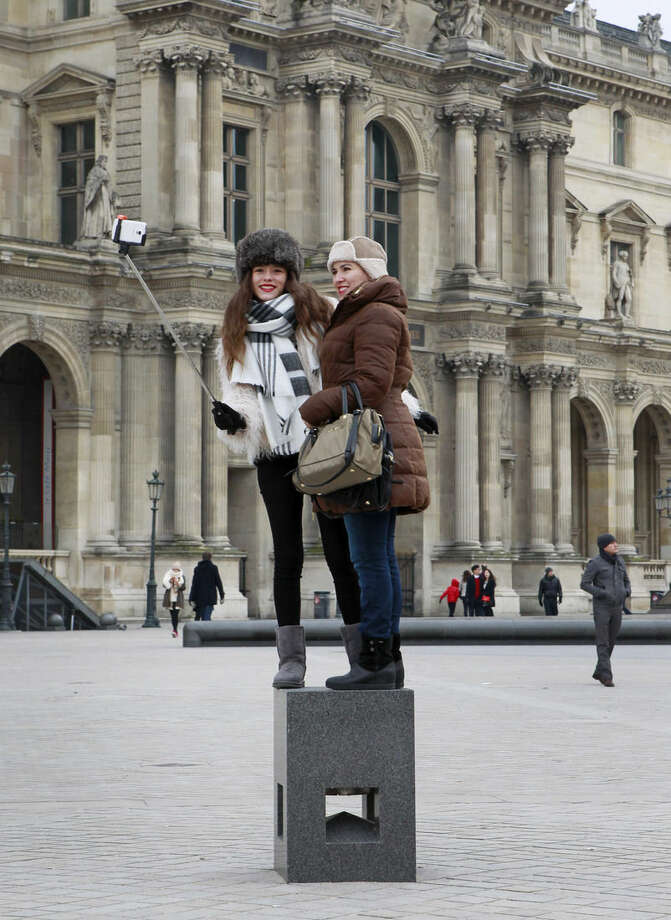 Tourists use a selfie stick outside the Louvre museum in Paris, Tuesday, Jan. 6, 2015. Selfie sticks have become enormously popular among tourists because you don't have to ask strangers to take your picture, and unlike hand-held selfies, you can capture a wider view without showing your arm. But some people find selfie sticks obnoxious, arguing that they detract from the travel experience. (AP Photo/Remy de la Mauviniere)