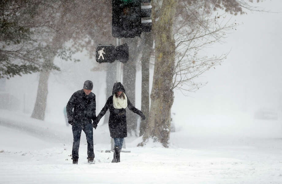 Andrew Loza, left, walks down a snow-covered sidewalk with Emily Olfson Sunday, Jan. 5, 2014, in St. Louis. Heavy snow continues to fall Sunday with forecasters calling for up to a foot (30 centimeters) in eastern Missouri and parts of central Illinois followed by bitter cold. (AP Photo/Jeff Roberson) / AP
