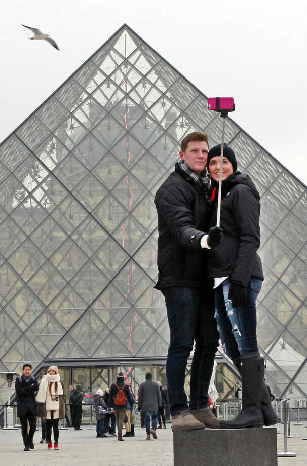 Chris Baker and Jennifer Hinson from Nashville, Tennessee, use a selfie stick in front of the Louvre Pyramide in Paris, Tuesday, Jan. 6, 2015. Selfie sticks have become enormously popular among tourists because you don't have to ask strangers to take your picture, and unlike hand-held selfies, you can capture a wider view without showing your arm. (AP Photo/Remy de la Mauviniere)