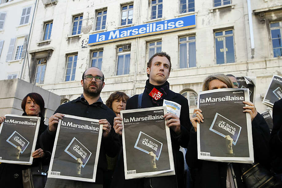 """Employees and journalists of the newspaper """"La Marseillaise"""" hold a journal of the day, reading"""" I am Charlie"""" , in front of the newspaper building during a minute of silence , in Marseille, southern France, Thursday, Jan. 8, 2015, a day after masked gunmen stormed the offices of a satirical newspaper and killed 12 people. French police hunted Thursday for two heavily armed men — one with a terrorism conviction and a history in jihadi networks — in the methodical killing of 12 people at a satirical newspaper that caricatured the Prophet Muhammad. The prime minister announced several overnight arrests and said the possibility of a new attack """"is our main concern."""" (AP Photo/Claude Paris)"""