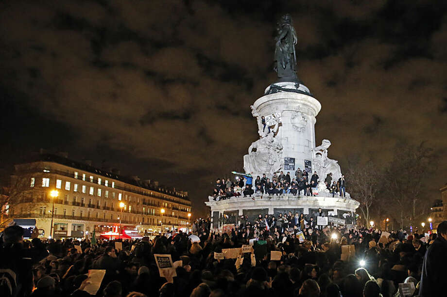 People gather around and ontop of the Republique Plaza statue during the solidarity demonstration in Paris, Thursday, Jan. 8, 2015. Scattered gunfire and explosions shook France on Thursday as its frightened yet defiant citizens held a day of mourning for 12 people slain at a Paris newspaper. French police hunted two heavily armed brothers suspected in the massacre, fearing they might strike again. (AP Photo/Francois Mori)