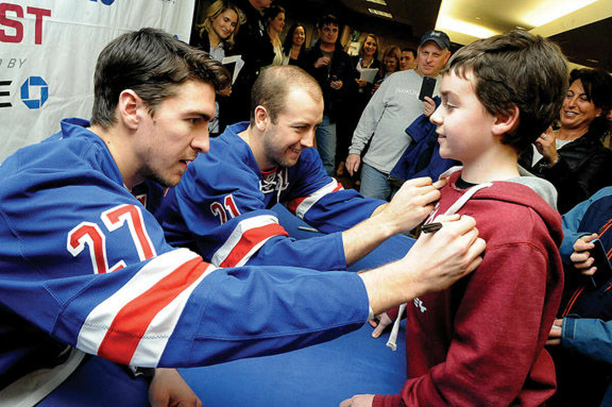 New York Rangers players Derek Stepan and Ryan McDonagh sign the shirt of young fan Matt Davis 11, at the Westport, CT Chase Branch on Tuesday. Hour photo/Matthew Vinci