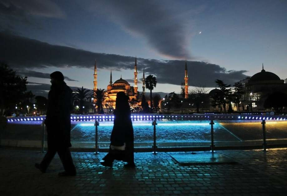 Tourists walk backdropped by the Sultan Ahmed Mosque, better known as the Blue Mosque, in the historic Sultanahmet district of Istanbul, following an explosion nearby, Tuesday, Jan. 12, 2016. The explosion killed several people and wounded 15 others Tuesday morning in the historic district of Istanbul popular with tourists. Turkish President Recep Tayyip Erdogan said a Syria-linked suicide bomber is believed to be behind the attack.(AP Photo/Lefteris Pitarakis)