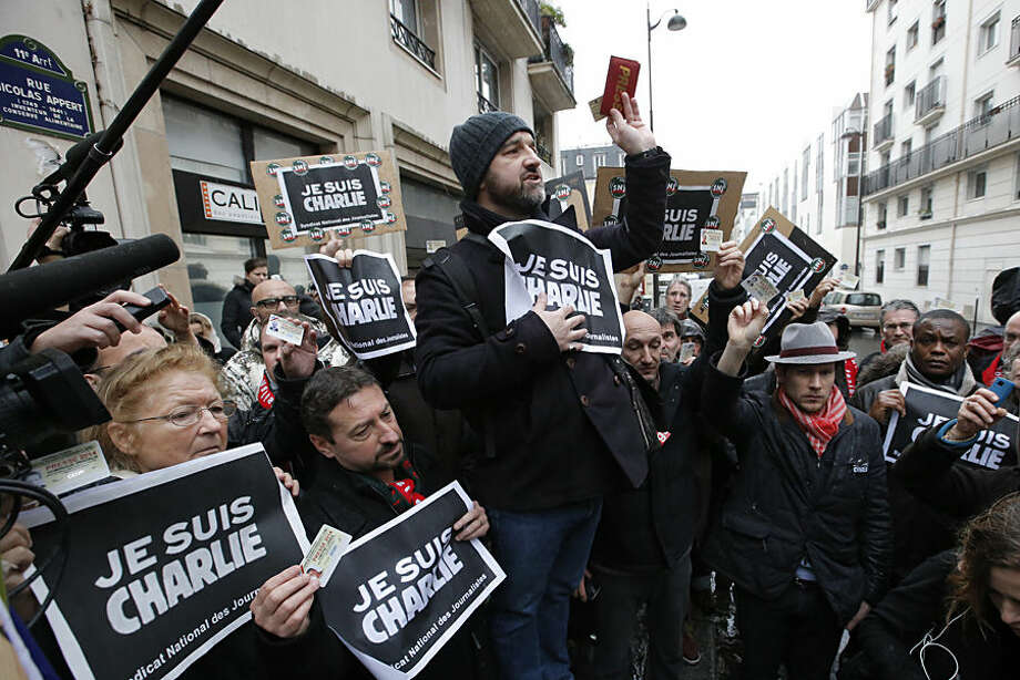 "Journalist hold up their press cards during a minute of silence outside the Charlie Hebdo newspaper in Paris, Thursday, Jan. 8, 2015, a day after masked gunmen stormed the offices of a satirical newspaper and killed 12 people. Protesters in some U.S. cities — repeating the viral online slogan ""Je Suis Charlie"" or ""I Am Charlie""— demonstrated against the deadly terror attack on a Paris newspaper office, joining thousands around the world who took to the streets to rally against the killings. (AP Photo/Francois Mori)"