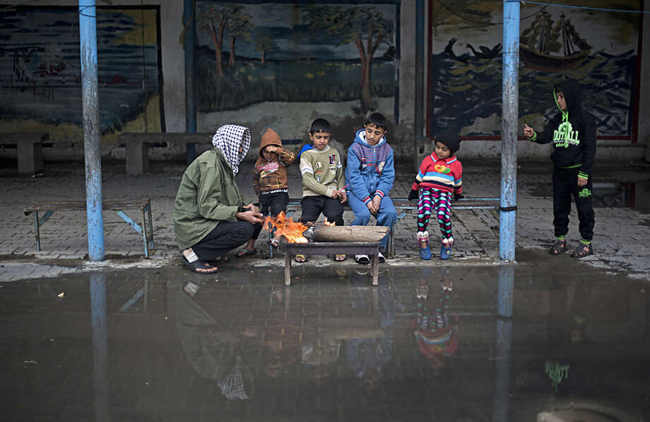 A Palestinian man sits with his children around fire to keep warm during a cold storm at a U.N. school where families live after their homes were destroyed by Israeli strikes in the summer, in Gaza City, Thursday, Jan. 8, 2015. (AP Photo/Khalil Hamra)
