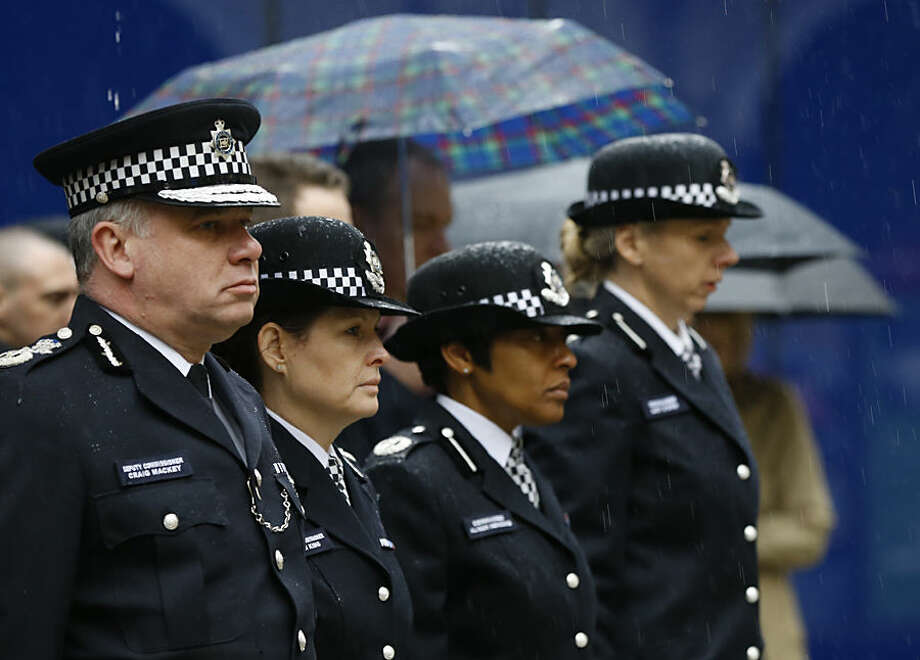 British police officers stand in the rain to hold a two minute silence to show their respect for all those murdered in Wednesday's terrorist attack in Paris, including two police officers, at New Scotland Yard in London, Thursday, Jan. 8, 2015. Masked gunmen stormed the Paris offices of a weekly newspaper that caricatured the Prophet Muhammad, methodically killing 12 people Wednesday, including the editor, before escaping in a car. It was France's deadliest postwar terrorist attack. (AP Photo/Kirsty Wigglesworth)