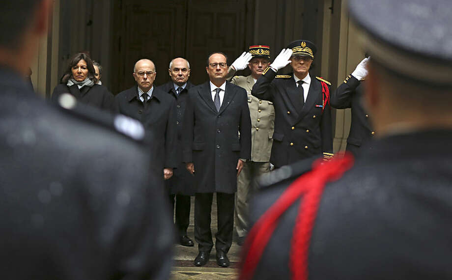 """French President Francois Hollande, center, with at his side interior minister Bernard Cazeneuve, left, and Paris police prefect Bernard Boucault, right, stands for a minute of silence, at Paris Prefecture in Paris, Thursday Jan. 8, 2015. French police hunted Thursday for two heavily armed men, one with a terrorism conviction and a history in jihadi networks, in the methodical killing of 12 people at a satirical newspaper that caricatured the Prophet Muhammad. The prime minister announced several overnight arrests and said the possibility of a new attack """"is our main concern."""" (AP Photo/Remy de la Mauviniere/Pool)"""