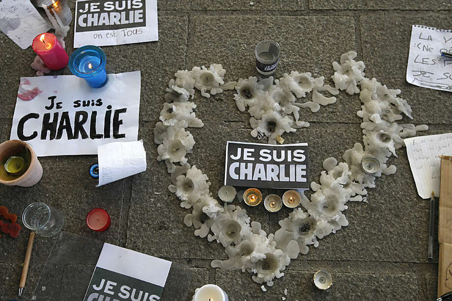 "A heart formed by melted candles is on the ground of the Old-Port to pay tribute to the victims of the satirical newspaper ""Charlie-Hebdo"", in Marseille, southern France, Thursday, Jan. 8, 2015, a day after masked gunmen stormed the offices of a satirical newspaper and killed 12 people. French police hunted Thursday for two heavily armed men — one with a terrorism conviction and a history in jihadi networks — in the methodical killing of 12 people at a satirical newspaper that caricatured the Prophet Muhammad. (AP Photo/Claude Paris)"